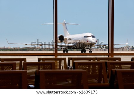 Business plane parked in an airport with seats on foreground. Focus on the plane.