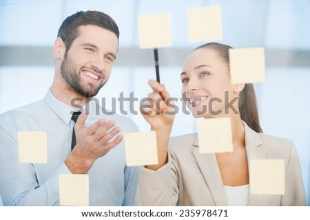 Business planning. Two cheerful business people discussing something while pointing adhesive notes attached to the glass  - stock photo