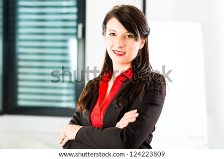 Business - Portrait of a businesswoman in business clothes in an Office, she smiles at the camera - stock photo