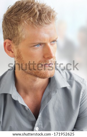 Business portrait of a handsome young smart man in bright office setting