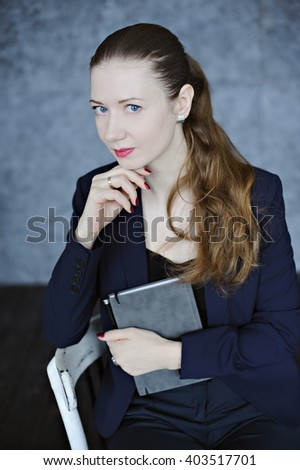 Business portrait of a young woman with diary and pen in hand. - stock photo