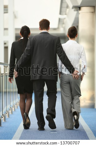 Business portrait of tree persons - young man and two women being touched by a man in modern office corridor - stock photo