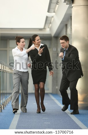 Business portrait of tree persons - young man and two women happy from success on modern office corridor - stock photo