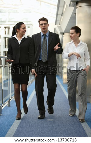 Business portrait of tree presons - young man and two women having nice chat talk on modern office corridor - stock photo