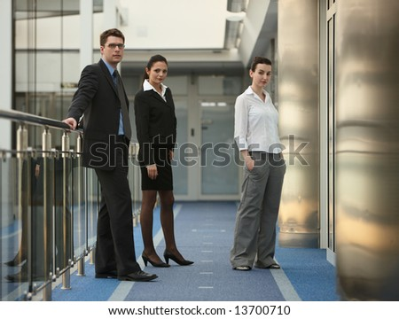 Business portrait of tree presons - young man and two women standing on modern office corridor - stock photo
