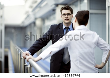 Business portrait - young man and woman standing and talking on modern office corridor