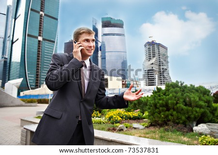 Business positive talks on the phone on the street - stock photo