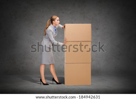 business, post and transportation concept - busy businesswoman pushing tower of cardboards