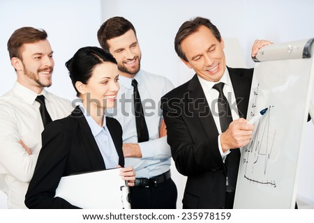 Business presentation. Confident mature businessman pointing graph on whiteboard and smiling while his colleagues standing near him and looking at sketch - stock photo