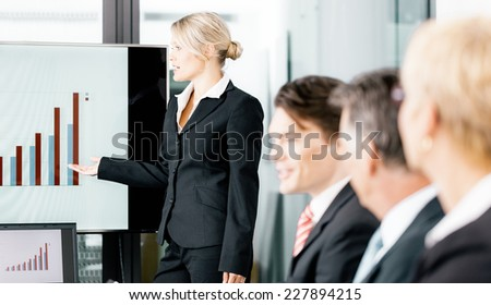 Business - presentation for the team, female, colleague is standing on the flipchart in office - stock photo