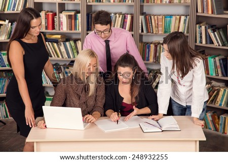 Business presentation on laptop computer. Business partners discussing documents and ideas at meeting. Brainstorming. Four women and one man have come together in the library. Students in practice. - stock photo