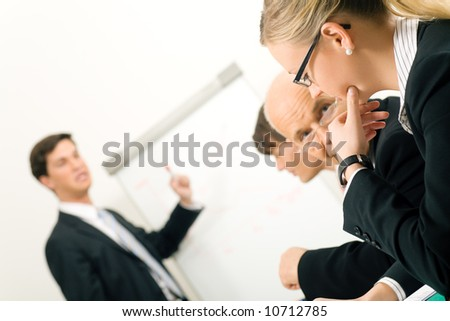 Business Presentation, two participants discussing. Very selective focus! Focus only on face of woman in front. - stock photo