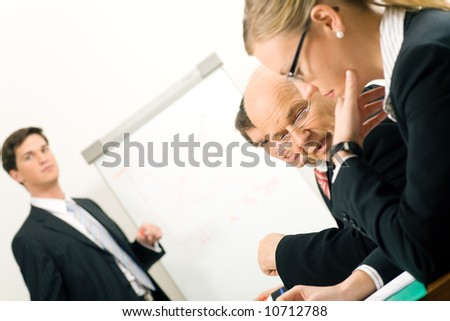 Business Presentation, two participants discussing. Very selective focus! Focus only on face of mature man in middle. - stock photo