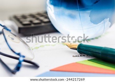 Business presentation with glboe and chart on the desk. - stock photo