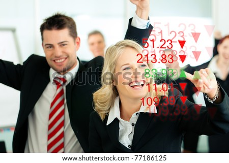 Business - presentation within a team; a female banker or consultant shows figures or share prices on screen - stock photo