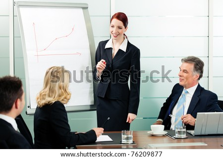 Business - presentation within a team; a female colleague is standing on the flipchart - stock photo