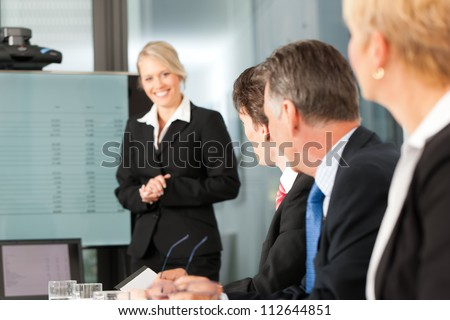 Business - presentation within a team, a female, colleague is standing on the flipchart, one man is looking into the camera - stock photo