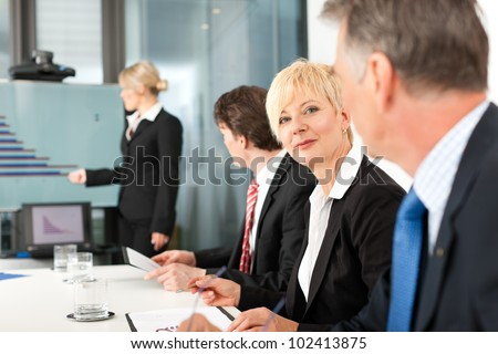 Business - presentation within a team, a female, colleague is standing on the flipchart, one woman is looking into the camera