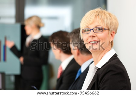 Business - presentation within a team; a female, colleague is standing on the screen - stock photo