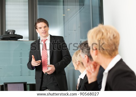 Business - presentation within a team; a male, colleague is standing on the flipchart - stock photo