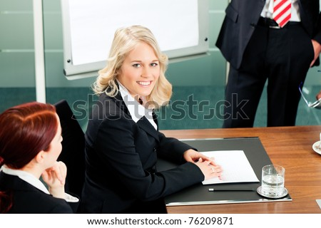 Business - presentation within a team meeting; a colleague is standing on the flipchart - stock photo