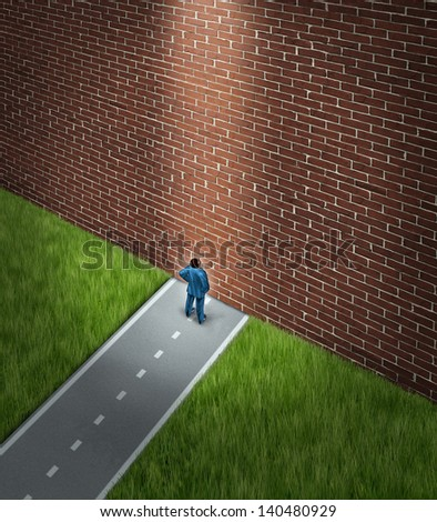 Business problems and conquering adversity concept as a confused businessman on a strategic journey meeting an obstacle and blocked by a huge brick wall with a light from above as a guide to freedom. - stock photo