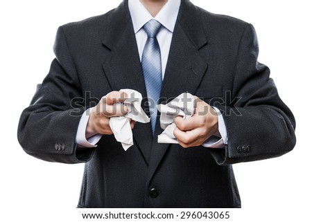 Business problems and failure at work concept - angry businessman in black suit hand holding crumpled torn paper document white isolated