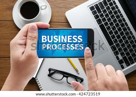 BUSINESS PROCESSES message on hand holding to touch a phone, top view, table computer coffee and book - stock photo