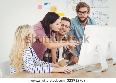 Business professionals discussing at computer desk in office - stock photo
