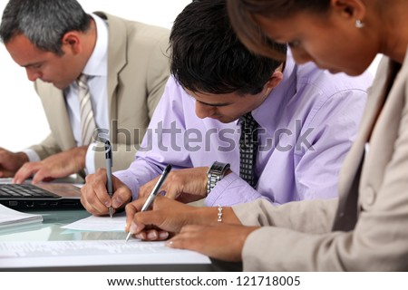 Business professionals filling in paperwork - stock photo