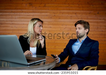 Business professionals having a discussion, businesspeople at meeting working with laptop, teamwork with businesspeople, attractive female boss and her employee discussing business project - stock photo