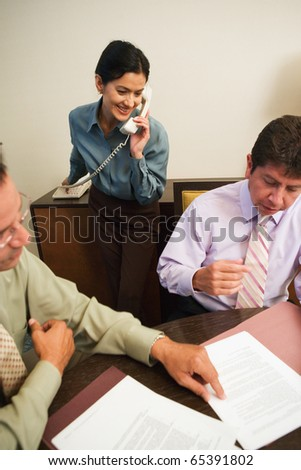 Business professionals reviewing paperwork - stock photo