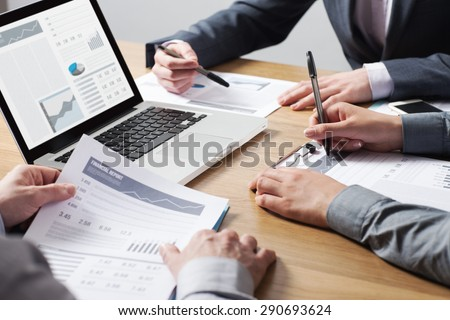 ... desk, hands close up pointing out financial data on a report, teamwork