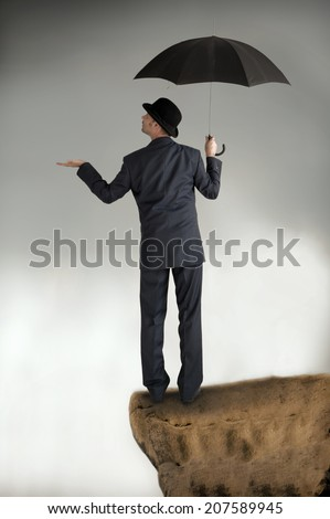 business protection concept businessman with umbrella feeling for rain - stock photo