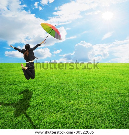 Business rainbow umbrella woman jumping to blue sky in grassland - stock photo
