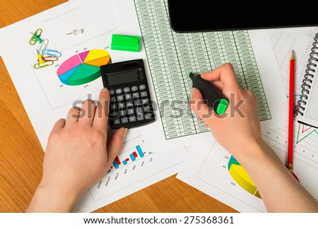 Business report. Above view of hands holding calculator over documents
