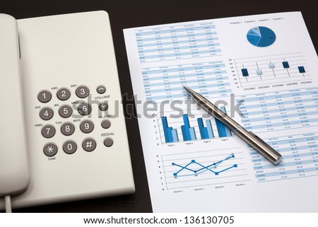 business report with telephone on a table