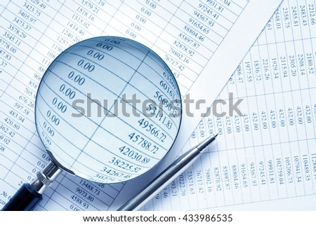 Business research. Closeup of magnifying glass and pen on paper with digits