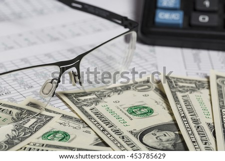 Business research. Closeup of spectacles, dollar bills, calculator on paper with digits