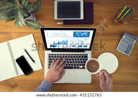 Business Research Data Economy Laptop and coffee cup in man work hands sitting on a wooden table - stock photo
