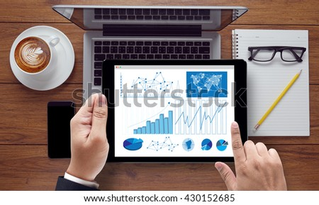 Business Research Data Economy , on the tablet pc screen held by businessman hands - online, top view - stock photo