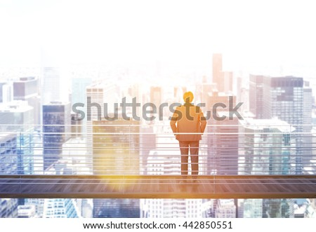 Business risk and research concept with back view of businessman standing on suspended bridge above New York city and looking into the distance. Side view. Toned image, 3D Rendering - stock photo