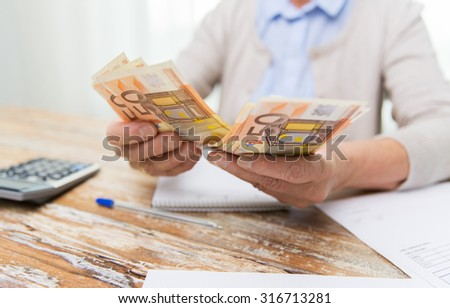 business, savings, annuity insurance, age and people concept - close up of senior woman with calculator and bills counting euro money at home - stock photo