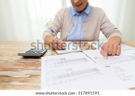 business, savings, annuity insurance, age and people concept - close up of senior woman with papers or bills and calculator writing at home - stock photo