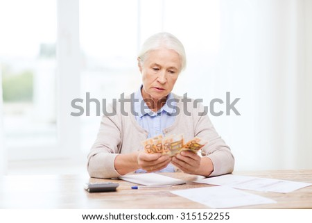 business, savings, annuity insurance, age and people concept - senior woman with calculator and bills counting euro money at home - stock photo
