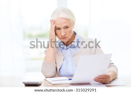 business, savings, annuity insurance, age and people concept - senior woman with papers or bills and calculator writing at home - stock photo