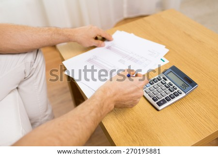 business, savings, finances and people concept - close up of man hands with papers and calculator at home