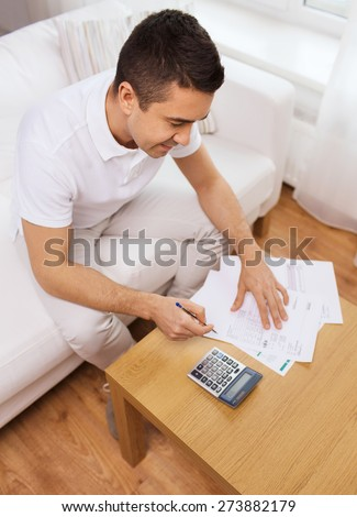 business, savings, finances and people concept - man with papers and calculator at home counting and filling tax form - stock photo