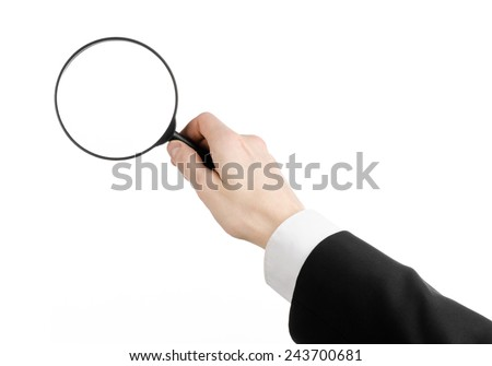 Business Search topic: businessman in a black suit holding a magnifying glass on a white isolated background - stock photo