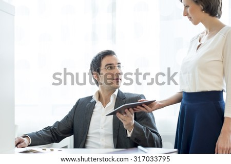 Business secretary giving a digital tablet to her superior in a white office setting. - stock photo